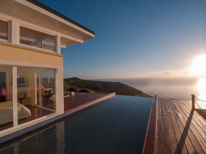 Luxurious coastal accommodation with sunrise view over the ocean from your bedroom in the North Island, New Zealand.