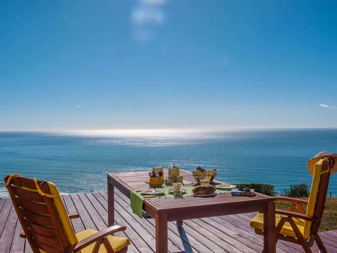 Your morning coffee with the calming private outdoor breakfast table overlooking the ocean in a boutique lodge, North Island, New Zealand