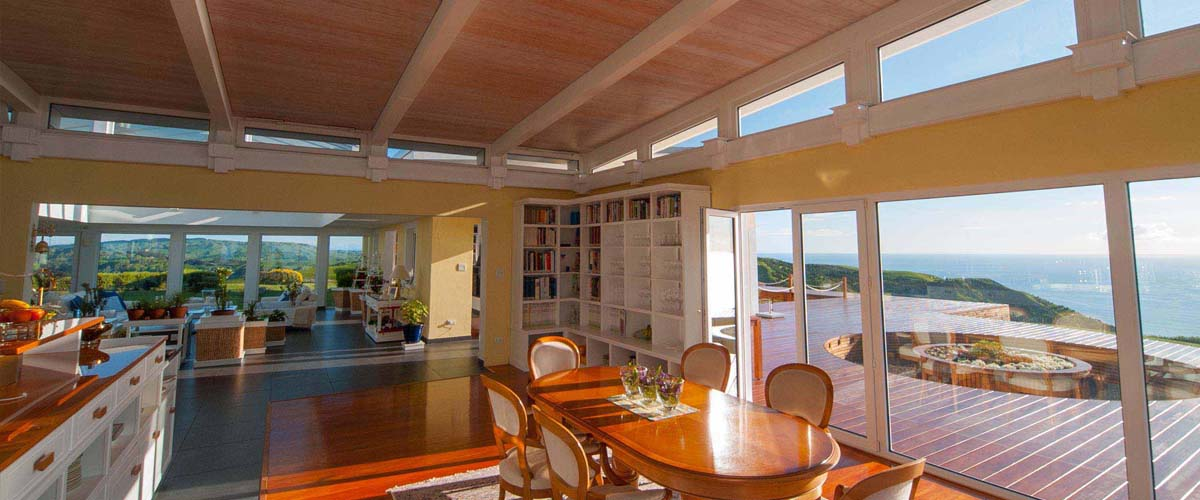 Oceanside stay, kitchen-dining area with cookbook library and view over the deck and the ocean. Atrium relaxing area with view over rolling hills into the valley