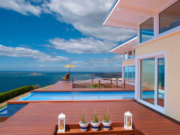 Two deck chairs at a luxurious oceanfront villa overlooking the ocean with aperitifs service