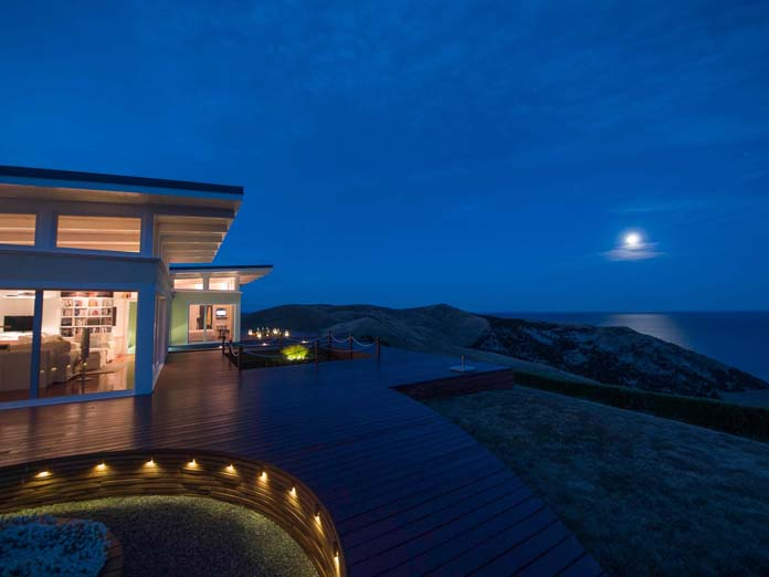 Picturequesue views over the ocean under moonlight and mood lighting on the expansive deck at the coast of New Zealand.