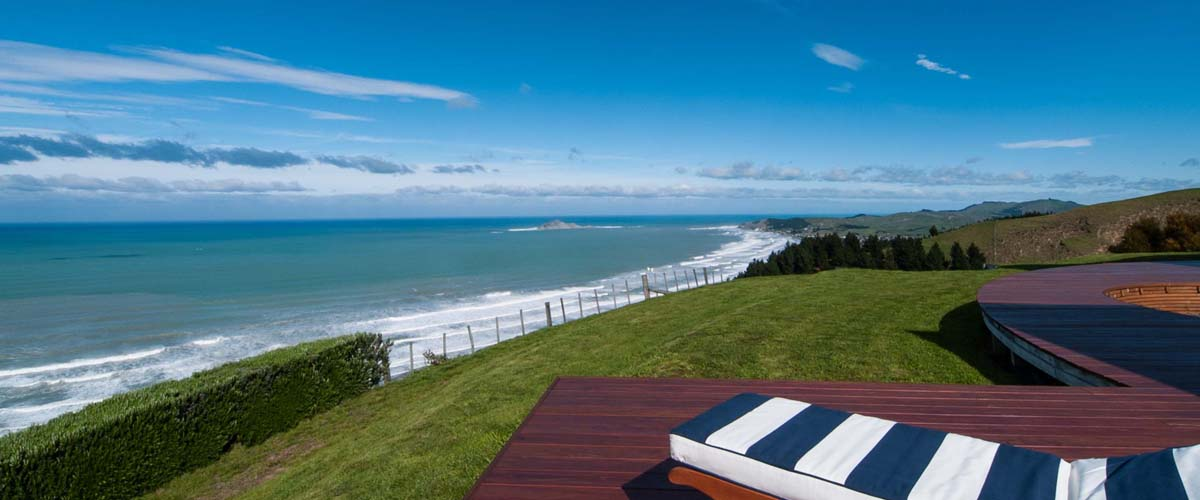 Sunlounger with comfortable cushions on the deck with a view over the Pacific ocean this is luxury escape in NZ