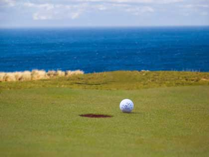 Golf ball near the hole at the golf course located on a cliff formation overlooking the oceans, Cape Kidnappers, New Zealand