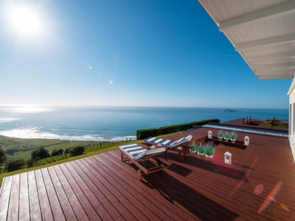 Two sun loungers facing the ocean on a private deck of a coastal accommodation in the North Island, New Zealand.